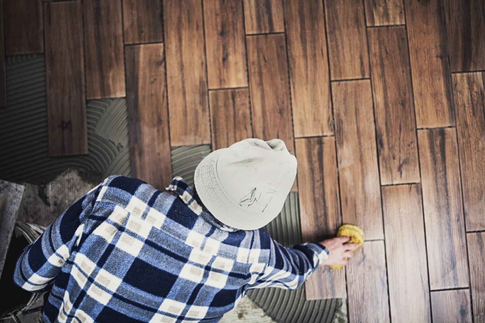 Mann reinigt Holzparkett
