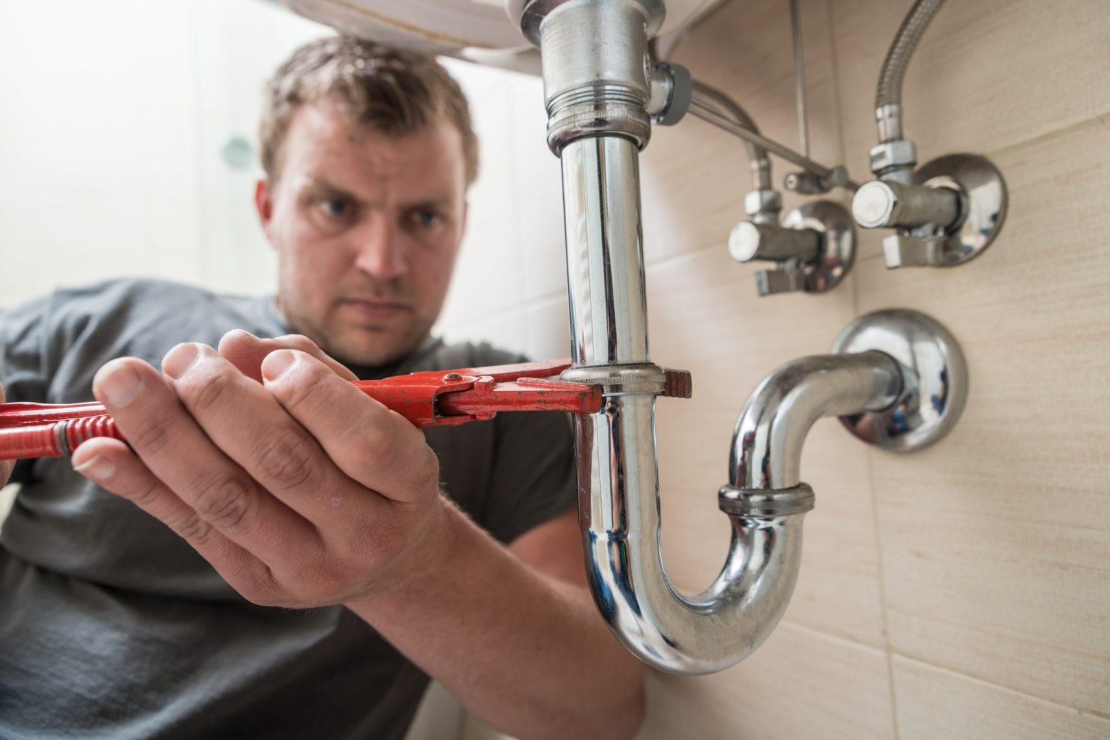 Mann repariert Waschbeckenabfluss