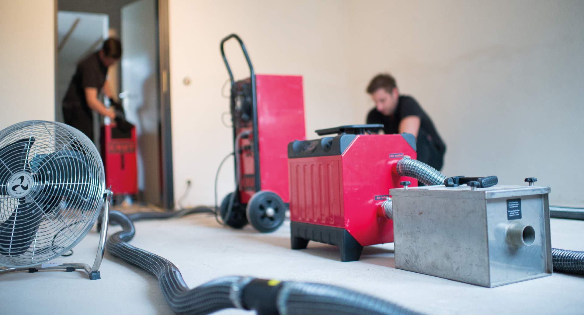 Rotes Trocknungsgerät steht im Raum und im Hintergrund arbeiten zwei Männer